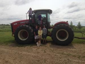Faith, Thomas, Ward, Jacquelin, Matt and Rosco the dog with the Hoculak's 2014 Versatile 450 tractor.